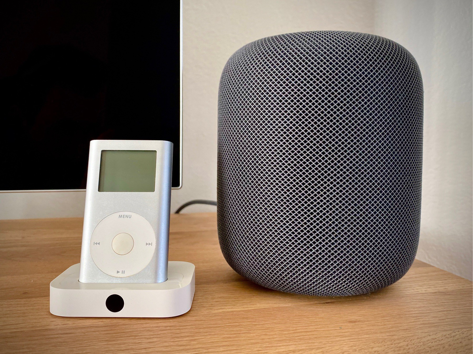 A silver iPod mini in an Apple Universal Dock sits next to a HomePod in space grey.