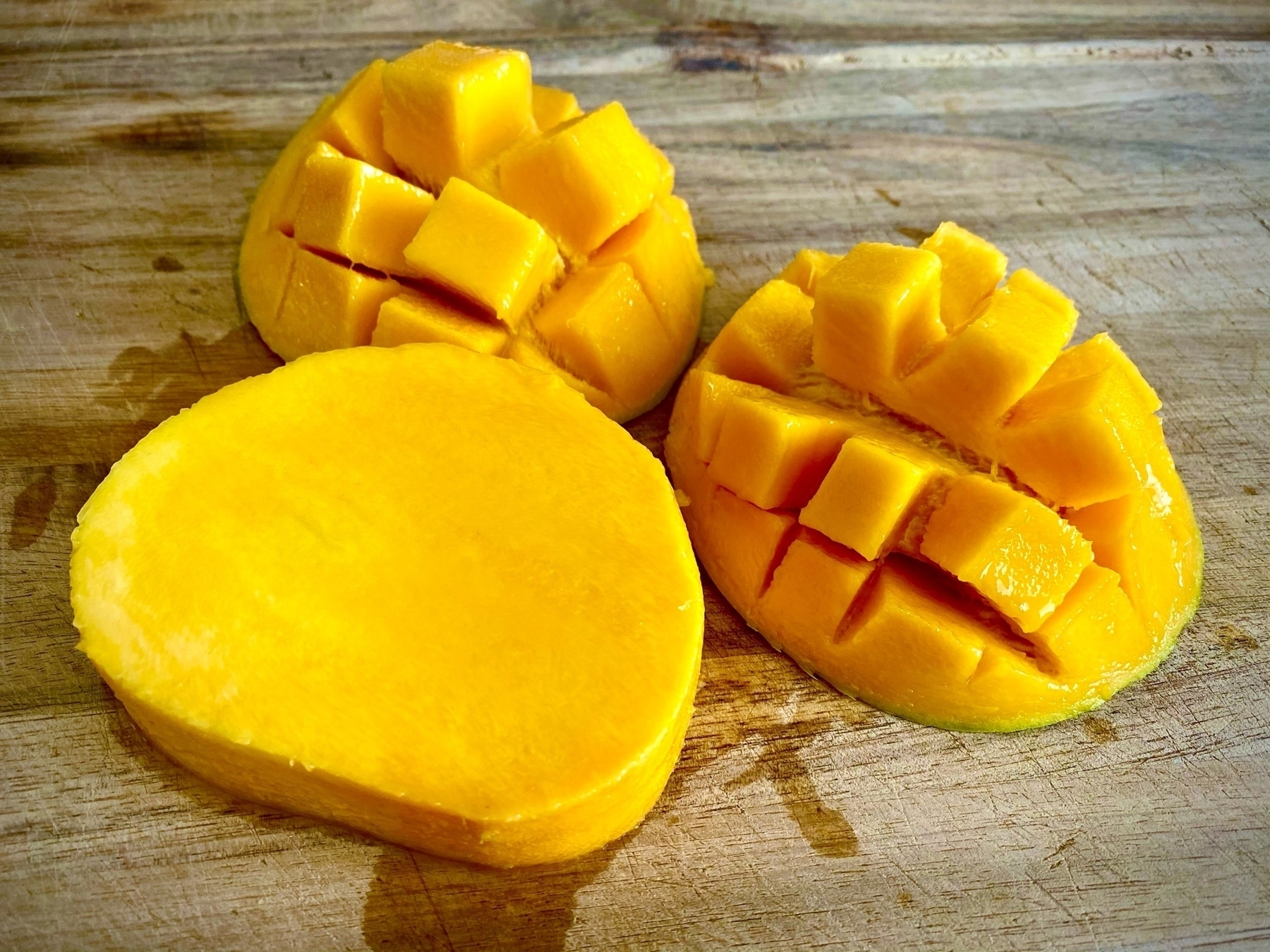 A mango sliced into thirds, two of which are hedgehog-style and one of which is the seed, all sitting on a wooden chopping board